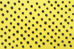 Top view of blueberries pattern on yellow background. Summer food concept Stock Images