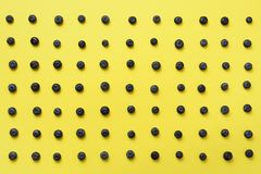Top view of blueberries pattern on yellow background. Summer food concept Royalty Free Stock Image
