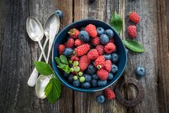 Top view of blueberries and raspberries in dark blue bowl. On old table Royalty Free Stock Photography