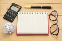 Top view blur fucus. glasses, round paper, empty notebook,calcul Stock Photos