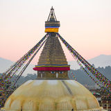 Top view of Bodhnath Stupa during sunset in Kathmandu with Buddha Eyes and prayer flags. Nepal. Royalty Free Stock Images
