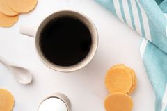 Top view of boiled egg in ceramic egg cup, cup of coffee and thin crispy corn chips on background of beautiful white peony. Breakfast concept. Copy space stock image