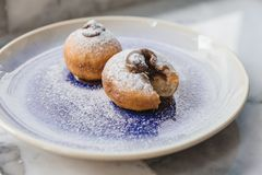 Top view of Bombolone is an Italian filled doughnut and is eaten as a snack food and dessert with hands cutting.  Stock Photography