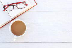 Top view book, glasses and coffee cup on white wooden table. Background Royalty Free Stock Images