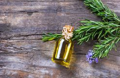 Top view Bottle glass of essential rosemary oil with rosemary branch and flower on wooden rustic background. Herbal oil concept stock images