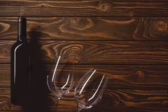Top view of bottle of red wine with empty glasses. On wooden table stock photo