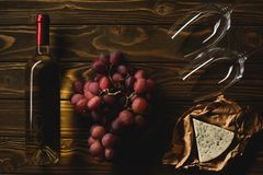 Top view of bottle of white wine with appetizers and wineglasses. On wooden table royalty free stock images