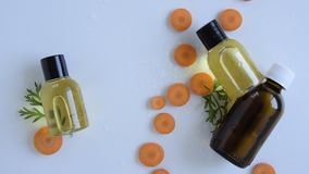 Top view of bottles with carrot essential oil. Healthy cosmetic product stock footage