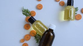 Top view of bottles with carrot essential oil. Healthy cosmetic product stock video footage