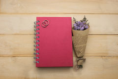 Top view bouquet flower and red cover notebook put on wooden flo Royalty Free Stock Image