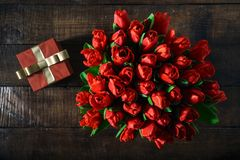 Top view bouquet red tulips red gift with copy space. Top view bouquet of red tulips with red gift box on dark wooden table with copy space Royalty Free Stock Photo