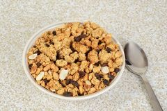 Top view bowl of granola raisin almond cereal with a spoon. On table Royalty Free Stock Photos