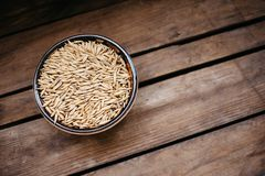 top view a bowl of oat grains on a wooden background, natural food royalty free stock images