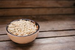 top view a bowl of oat grains on a wooden background, natural food royalty free stock photos