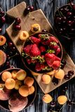 top view of bowls with cherries strawberries peaches and apricots on wooden royalty free stock photo