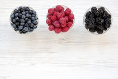 Top view, bowls containing berries: blueberries, blackberries, raspberries. Healthy eating and dieting. From above, overhead. Copy space and text area royalty free stock photos