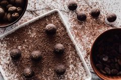 top view of bowls with nutmegs and cocoa beans, plate with truffles covering by grated chocolate royalty free stock photography