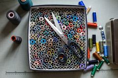 Top view of the box with colored threads on which are large scissors. Sewing industry royalty free stock photo