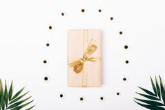 Top view of a box with a gift and a gold ribbon and palm branche Royalty Free Stock Photo