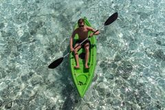 Young happy man kayaking on a tropical island in the Maldives. Clear blue water royalty free stock images
