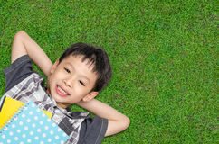 Top view of boy smiles and lying on grass field Stock Images