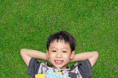 Top view of boy smiles and lying on grass field Stock Image