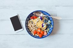 Top view of brakfast bowl and smart phone royalty free stock images