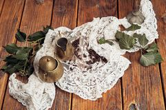 A top view of a brass milk jug and a brass sugar bowl, presented on an old, wooden table top with a white tablecloth royalty free stock images