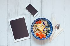 Top view of breakfast bowl, smart phone and digital tablet royalty free stock photography
