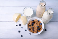 Top view on a breakfast with cornflakes blueberries and fresh dairy. Top view on a breakfast with cornflakes blue berries and fres dairy on a white wooden Royalty Free Stock Photography