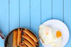 Top view of breakfast meal ,Fried sausages in black pan and fried eggs in white dish on blue wooden table, have copy space for put. Text Royalty Free Stock Photography