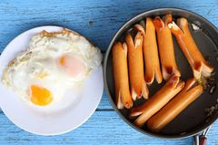 Top view of breakfast meal ,Fried sausages in black pan and fried eggs in white dish on blue wooden table. Look delicious Stock Photos