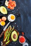 Top view of breakfast table with fried eggs, avocado, asparagus,. Red caviar and smoked salmon, copy space Stock Photo