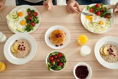 Top view of breakfast table with healthy food for couple. Dining table with food, couple enjoying delicious homemade meal together, men and women have pancakes Stock Images