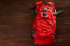 Top view of the bright orange travel backpack on a wooden background. Stock Photos