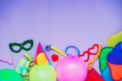 Top view bright party tools and decoration - baloons, funny carnival masks, festive tinsel on lilac background. Happy birthday gre. Eting card. Purim. Design royalty free stock photos