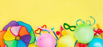 Top view bright party tools and decoration - baloons, funny carnival masks, festive tinsel on yellow background. Happy birthday gr. Eeting card. Design concept stock photography