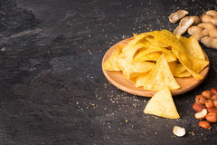 Top view of bright yellow nachos on a light wooden round plate. Corn chips with mixed nuts on a black background. royalty free stock images