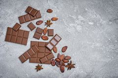 Top view of broken chocolate bars with cocoa beans and anise stars as ingredient for confectionery