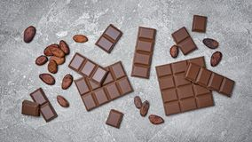 Top view of broken chocolate bars with cocoa beans as ingredient for confectionery