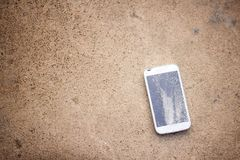 Top view of broken mobile phone drop on cement floor. With copy space for desing, High Contrast, Shallow Depth of Field, vintage tone royalty free stock image