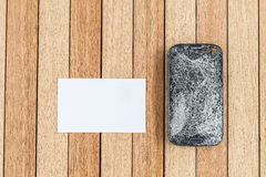 Top view broken of smart phone and blank paper on wooden table. Background royalty free stock image