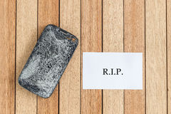 Top view broken of smart phone and blank paper on wooden table. Background stock image