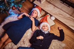 Top view, brother and sister lying on a fur carpet in a living room decorated for Christmas. royalty free stock images