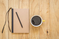Top view of brown book and coffee cup on wooden table Royalty Free Stock Photography