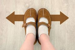 Top View of Brown Boot with Different Brown Decision Arrow. A Pair of Feet Standing. Shoes Walking Direction on Wooden. Floor Background royalty free stock photography