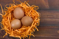 Brown eggs in a decorative nest on a wooden background. Top view brown eggs in a decorative nest on a wooden background royalty free stock photo
