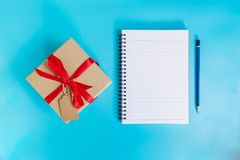 Top view brown gift box and notebook paper for new year on blue Stock Photos