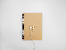 Top view brown notebook and earphone. Top view brown notebook and earphone on white background stock photography
