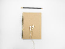 Top view brown notebook and earphone. Top view brown notebook and earphone on white background royalty free stock photography